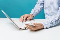 Mains, carnet et Smart-téléphones masculins pour des affaires dans le bureau sur le fond bleu Images stock