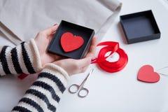 Mains caucasiennes blanches jugeant le jouet en forme de coeur dans la boîte sur gagné Photographie stock libre de droits