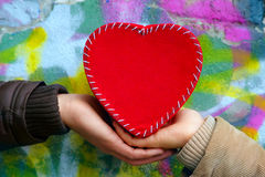 Mains ce coeur rouge de la participation une sur le fond de mur Photos libres de droits