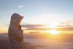 Mains chr?tiennes de femme priant ? un dieu sur le fond de montagne avec le lever de soleil de matin La femme prient pour un dieu photographie stock