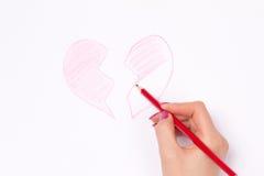 Mains, coeur coupé et crayon Images libres de droits