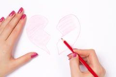 Mains, coeur coupé et crayon Photographie stock