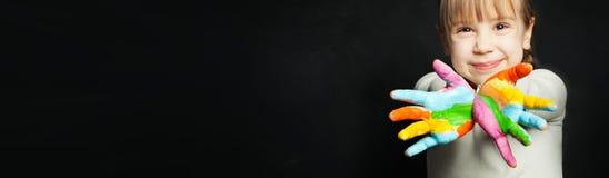 Mains colorées colorées de fille heureuse de petit enfant sur le fond de tableau noir de salle de classe images stock