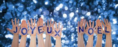 Mains construisant Joyeux Noel Means Merry Christmas, fond de scintillement de Bokeh image libre de droits