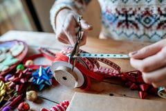 Mains coupant le ruban pour envelopper des cadeaux Photo libre de droits