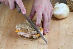 Mains coupant le sandwich Images libres de droits