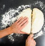 Mains coupant un morceau de pâte avec le couteau Photos stock