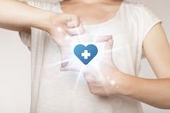 Mains créant une forme avec la croix de bleu de coeur Images libres de droits