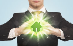 Mains créant une forme avec la maison verte Photo libre de droits