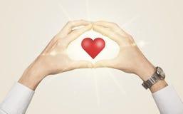 Mains créant une forme avec le coeur brillant Photo libre de droits
