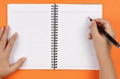 Mains, crayon lecteur et cahier Photographie stock