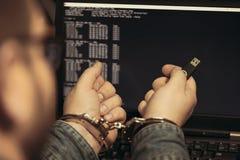 Mains criminelles de pirate informatique verrouillées dans des menottes Vue de plan rapproché photographie stock