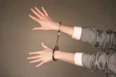 Mains criminelles verrouillées dans des menottes image libre de droits