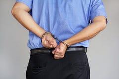 Mains criminelles verrouillées dans des menottes Vue de plan rapproché photographie stock