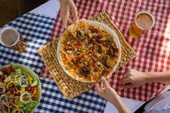 Mains cultivées sur des amis ayant la pizza à la table Photo libre de droits
