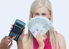 Mains cultivées utilisant la calculatrice et la belle femme tenant des devises se tenant contre le backgro blanc Image stock
