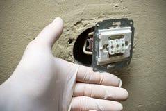 Mains d'électricien dans les gants installant l'interrupteur de lampe dans le mur photographie stock
