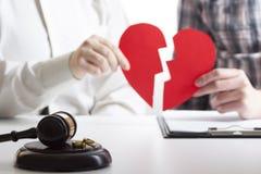 Mains d'épouse, décret de mari du divorce de signature, dissolution, décommandant le mariage, documents de séparation juridique,  images libres de droits