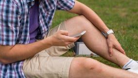 Mains d'étudiant avec le téléphone portable. Photos stock