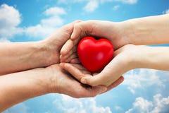 Mains d'aîné et de jeune femme tenant le coeur rouge Images libres de droits