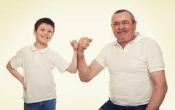 Mains d'aîné et de muscle d'exposition d'enfants Photo stock