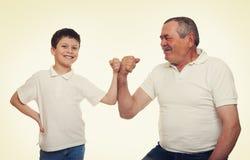 Mains d'aîné et de muscle d'exposition d'enfants Photo libre de droits