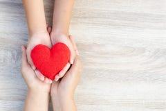 mains d'adulte et d'enfant tenant le coeur rouge fait main sur le fond en bois photo libre de droits