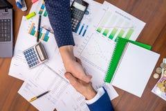 Mains d'affaires secouant au-dessus du graphique de gestion photographie stock libre de droits