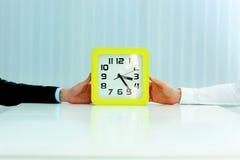 Mains d'affaires tenant des horloges Images libres de droits