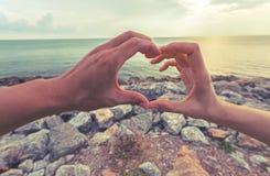 Mains d'amant sous forme de coeur contre le ciel avec le fond de silhouette Photographie stock