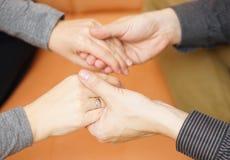 Mains d'ami tenant des mains d'amie Émotions et appui c Images libres de droits