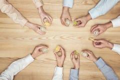 Mains d'amis avec des tirs de tequila sur le dessus de table en bois Image stock