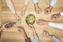 Mains d'amis avec des tirs de tequila sur le dessus de table en bois Photo libre de droits