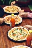 Mains d'amis prenant des tranches de pizza Images stock