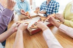 Mains d'amis prenant des tranches de pizza Photo stock