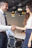 Mains d'And Businesswoman Shaking d'homme d'affaires dans la salle de réunion moderne avec des collègues se réunissant autour du  photo stock