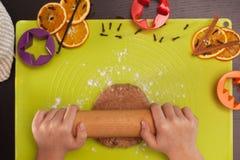 Mains d'enfant étirant la pâte de biscuits de pain d'épice Photographie stock