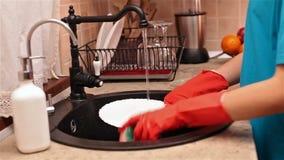 Mains d'enfant avec les gants en caoutchouc lavant un plat clips vidéos