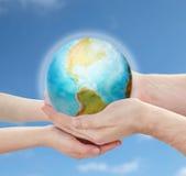 Mains d'enfant et de père tenant la planète de la terre Images libres de droits