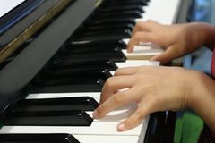 Mains d'enfant jouant le piano photos stock
