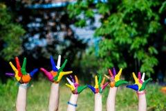 Mains d'enfant peintes dans des couleurs lumineuses d'isolement sur le fond de nature d'été Images libres de droits