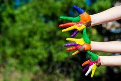 Mains d'enfant peintes dans des couleurs lumineuses d'isolement sur le fond de nature d'été Photographie stock libre de droits