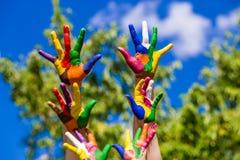 Mains d'enfant peintes dans des couleurs lumineuses d'isolement sur le fond de nature d'été Photo libre de droits