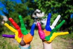 Mains d'enfant peintes dans des couleurs lumineuses d'isolement sur le fond de nature d'été Image stock