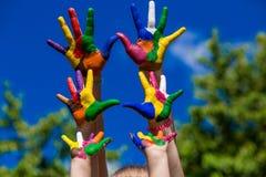 Mains d'enfant peintes dans des couleurs lumineuses sur le fond de nature d'été Photo libre de droits