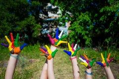 Mains d'enfant peintes dans des couleurs lumineuses sur le fond de nature d'été Image libre de droits