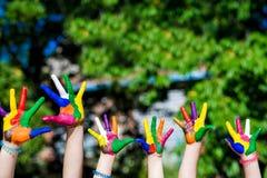 Mains d'enfant peintes dans des couleurs lumineuses sur le fond de nature d'été Image stock
