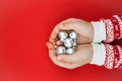 Mains d'enfant tenant les babioles argentées de Noël images stock