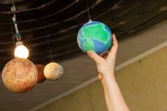 Mains d'enfants avec les planètes du système solaire images libres de droits