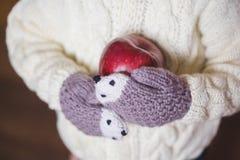 Mains d'enfants dans des mitaines confortables tenant la pomme rouge Image libre de droits